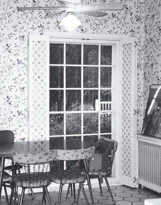 black and white before photo of a dining room area with wallpaper