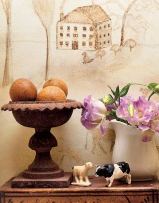 mural with new england scene behind a table with vase animal figurines and urn