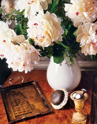 peonies in a white pitcher on a table with a tray and other trinkets