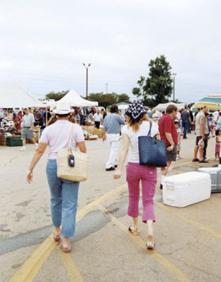 two women walking towards a flea market with tented booths