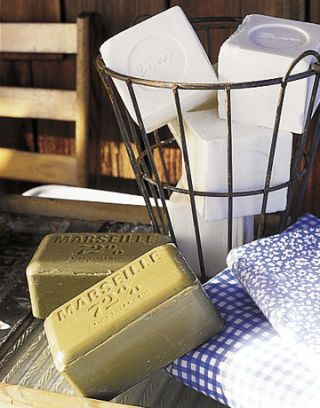 wire basket with cubes of white soap next to olive green bars of soap