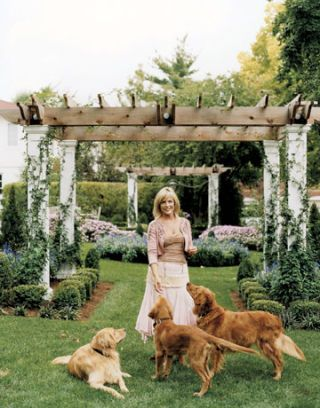 woman with three dogs in a garden with arbors