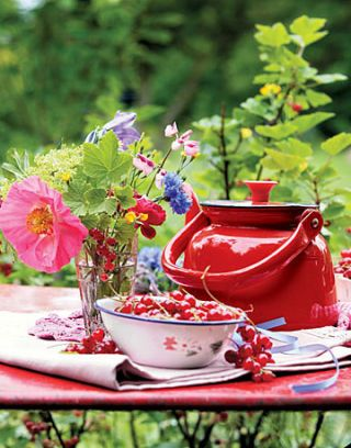 bowl of fresh currants on a table with a red tea pot and vase of flowers