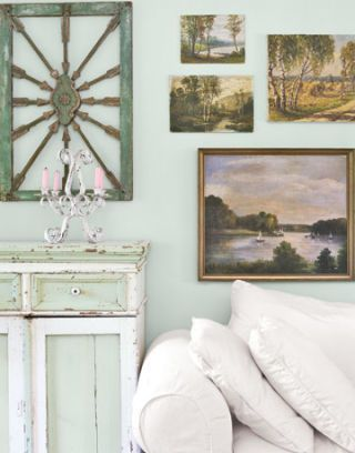 landscape paintings on a pale aqua wall above a white couch
