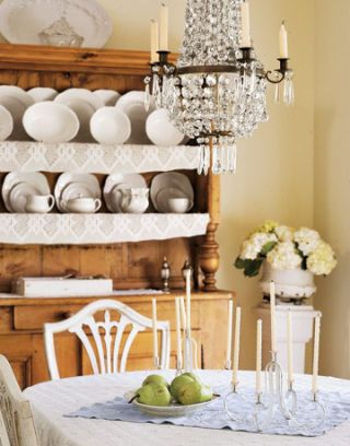 white china displayed in a wood hutch behind a dining table below a chandelier