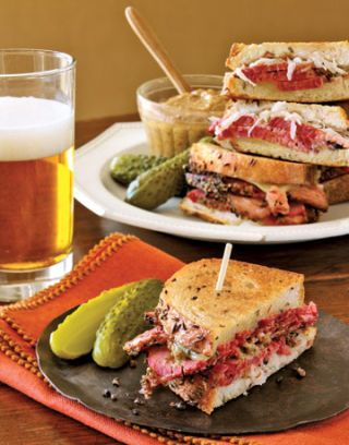 pastrami sandwich halves and pickles on plates next to a glass of beer
