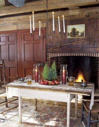 dining table with candles underneath a candelabra and near a fireplace