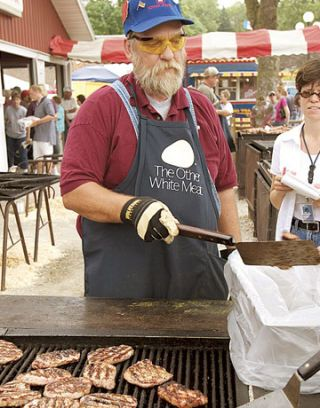 man barbecuing pork chops on a grill