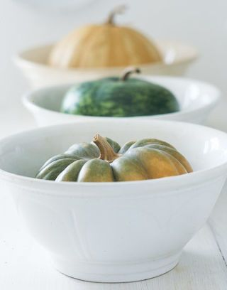 three different colored small pumpkins in white bowls