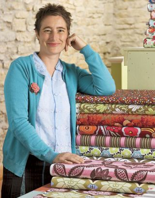 woman smiling next to stacked bolts of fabric
