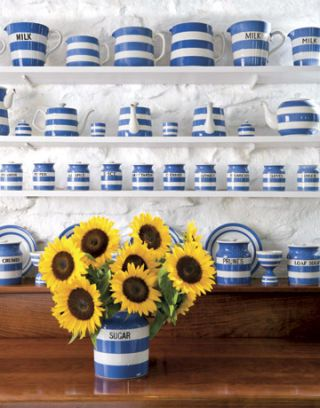 shelves of cornish ware displayed behind a pitcher of sunflowers