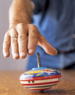 hand above a colorful spinning top