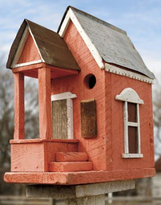 red birdhouse with steps and a porch