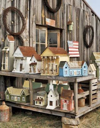 a variety of birdhouses on display on a wood display stand next to a barn