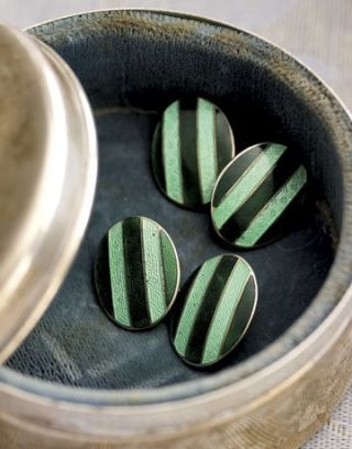 striped light and dark green cuff links in a round case