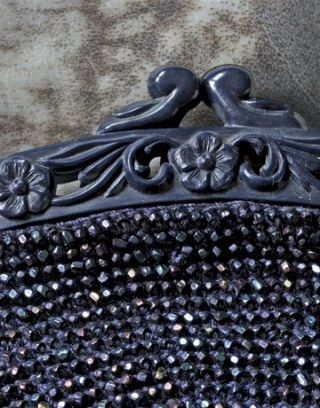 close up of flower carved snap clasp on a vintage beaded purse