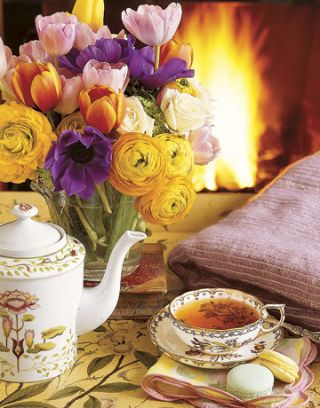 flowers and tea set in front of a fire