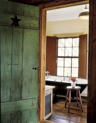 green door with star leading into bathroom with iron tub