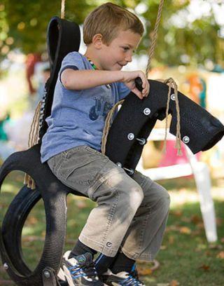 child on tire horse