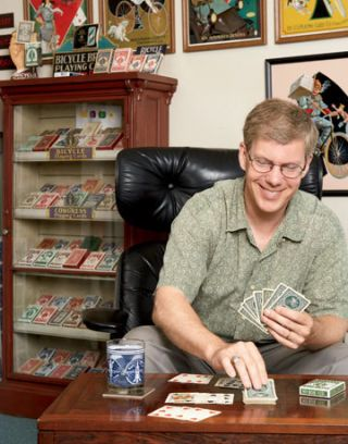 man playing cards in front of a card display case