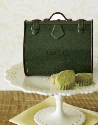 green biscuit tin with handle on cake platter