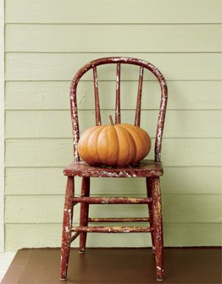 pumpkin on top of wooden red chair