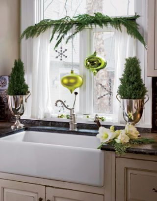 white apron sink surrounded by green holiday decorations