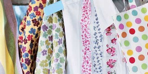 multicolored floral and polka dot tote bags hanging on hooks with white blouse