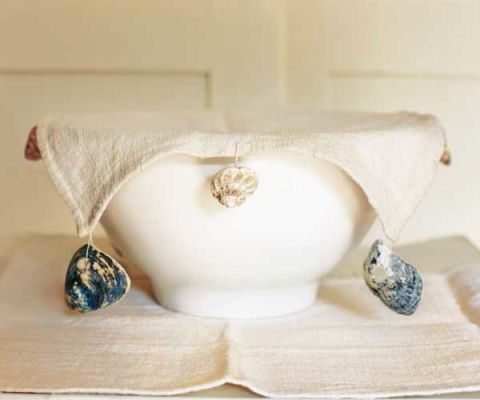 an off white linen bowl cover on top of white bowl with shells sewn on sides to anchor