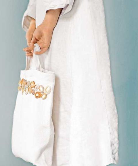 woman in white linen dress holding white tote bag with seashells sewn on