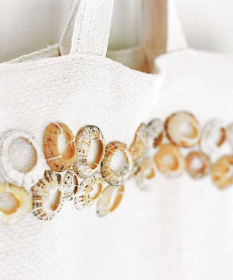close up of limpet shells sewn on to white tote bag
