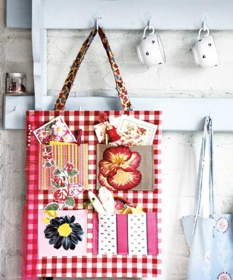 a red gingham tote bag with many pockets hanging from white hook