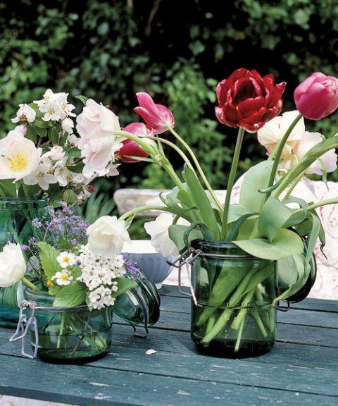 different arrangements of tulips in glass jars