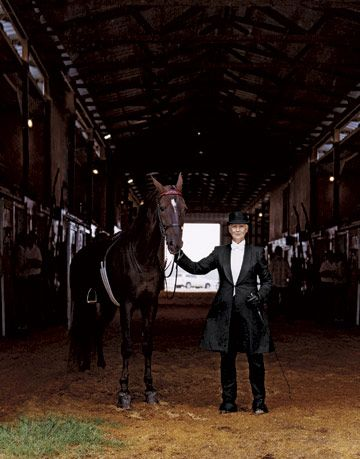 Sandy, a Chardonnay owner, wears formal gear posing with horse