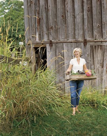 woman carrying a tray of flowers in front of a wood barn