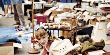 two women looking through boxes at a flea market