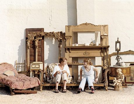 two women sitting on an antique couch frame surrounded by antique furniture