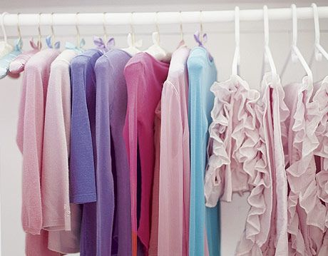 pastel colored clothes hanging in a white closet