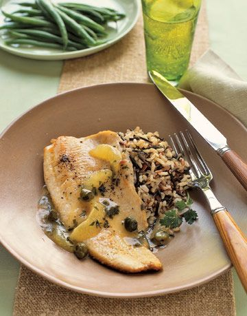 cooked trout with lemon and wild rice next to a plate of green beans