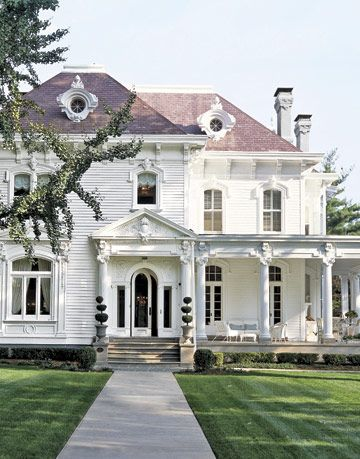 grand white two story beaux arts style home with manicured lawn