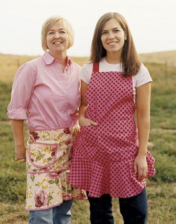 two women in aprons in a field