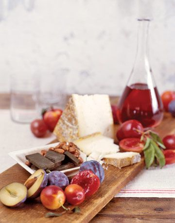 plums on a wood tray next to cheese and chocolate