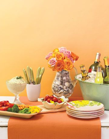 simple buffet with vegetables and roses in a pitcher on an orange tablecloth