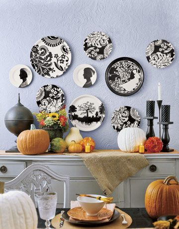 black and white graphic plates on a wall above a halloween decorated table