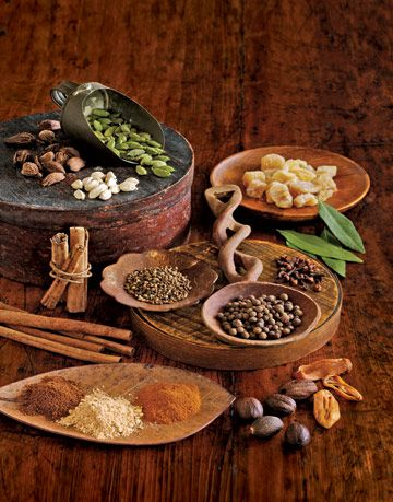 spices and beans in wooden dishes on a wood surface