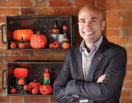 man smiling in front of his pumpkin candle collection