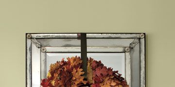 autumn wreath made of leaves above a mantel with small pumpkins