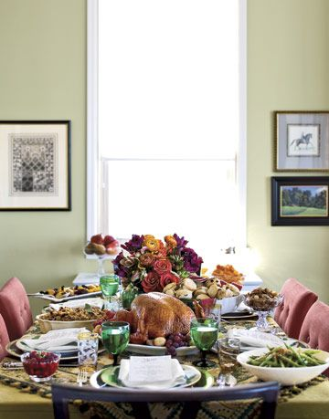 thanksgiving table with a turkey and flowers and side dishes