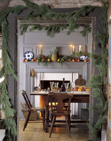 doorway with garland around the edge leading into a room with a fireplace