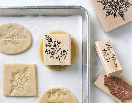 a tray of sugar cookie cutouts surrounded by rubber stamps